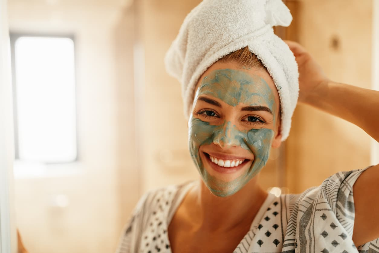 woman smiling with face scrub